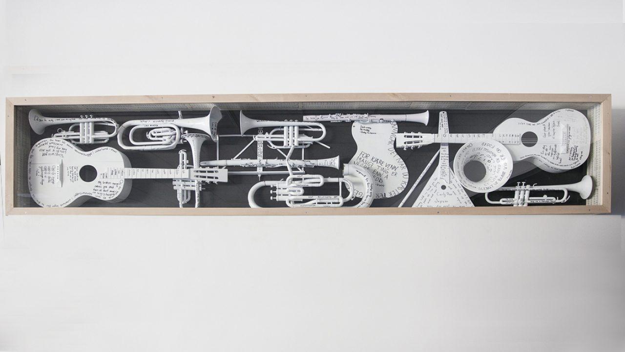 Hvitmalte musikkinstrumenter med påskrevne sitater fra elever, montert som relieff på veggen.
