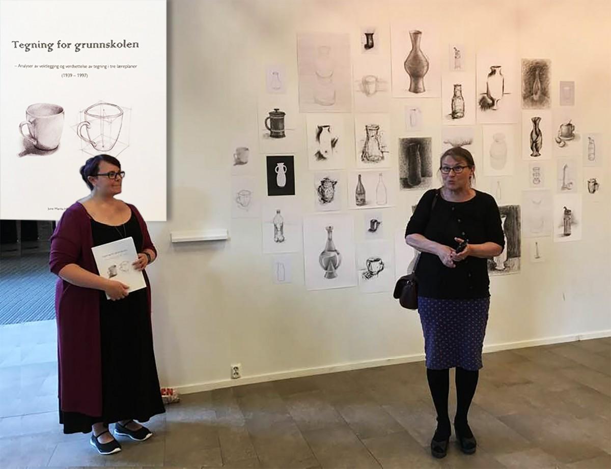 To kvinner i samtale forran vegg med tegninger av ulike objekter.