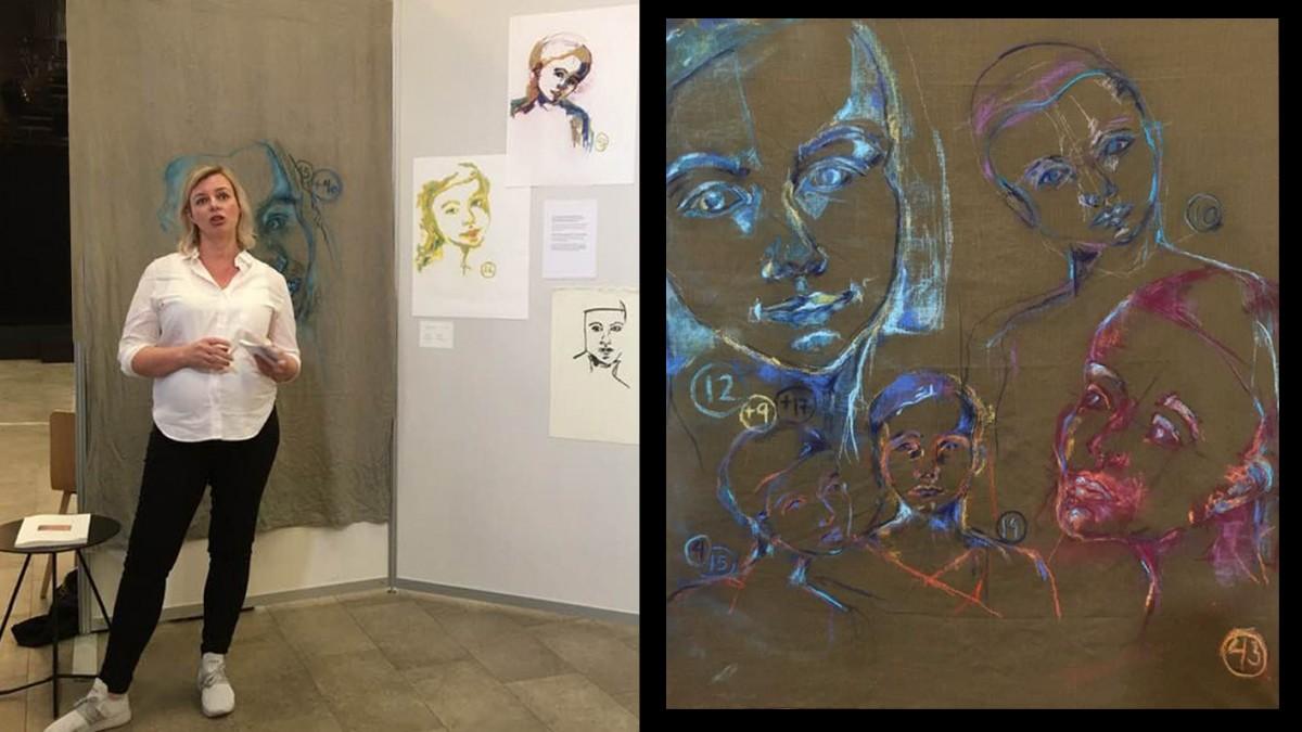 Kvinne foran vegg med pastelltegninger.