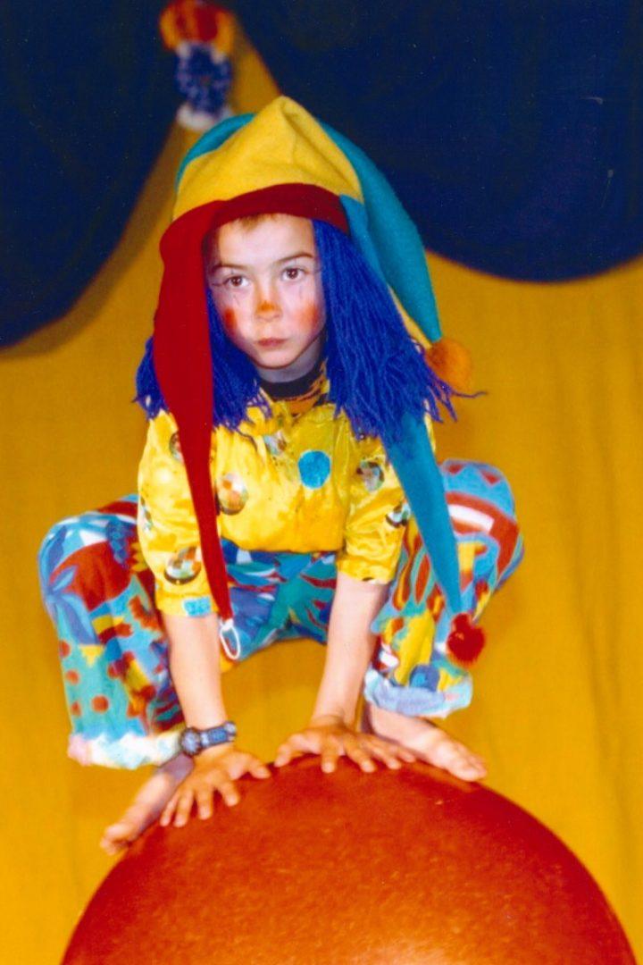 Gutt med fargerike klær på ball