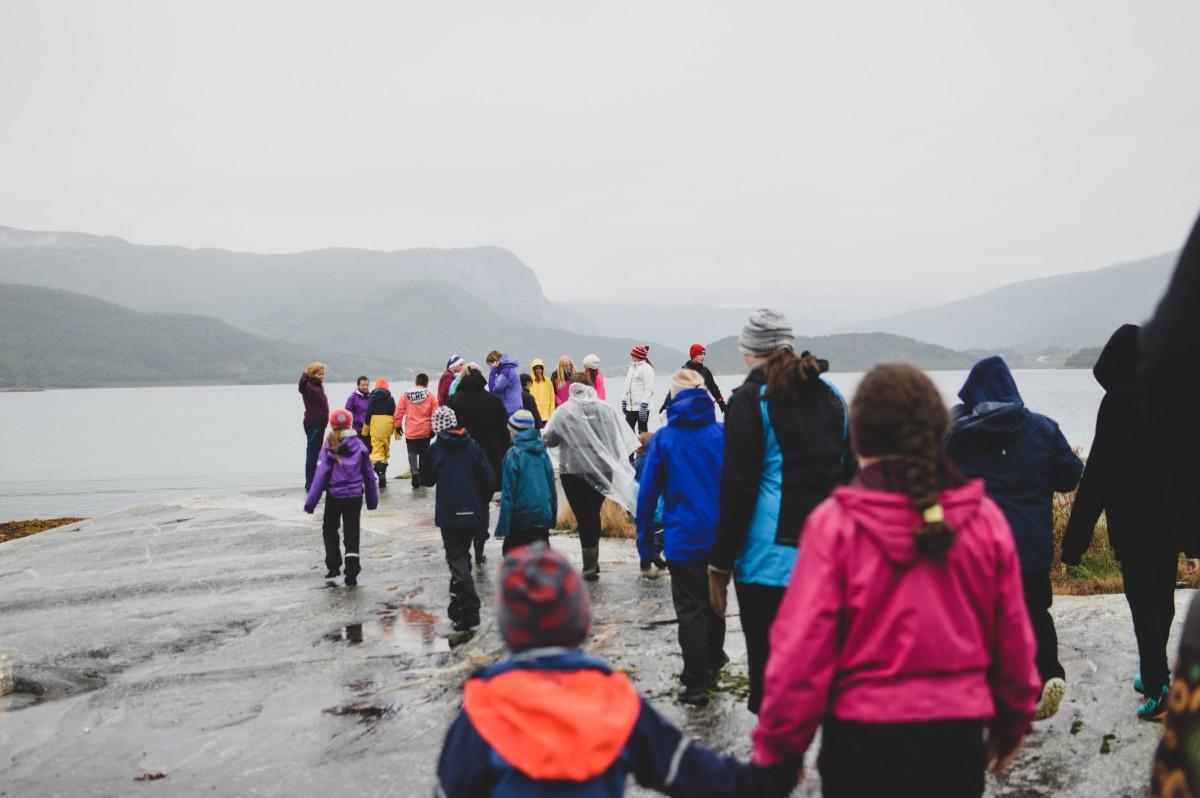 Barn og voksne som går mot havet på berg.