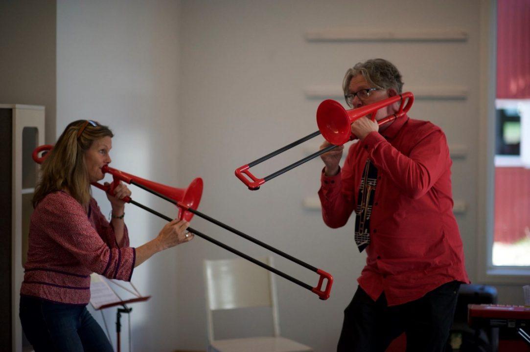 Dame og mann spiller på røde tromboner.