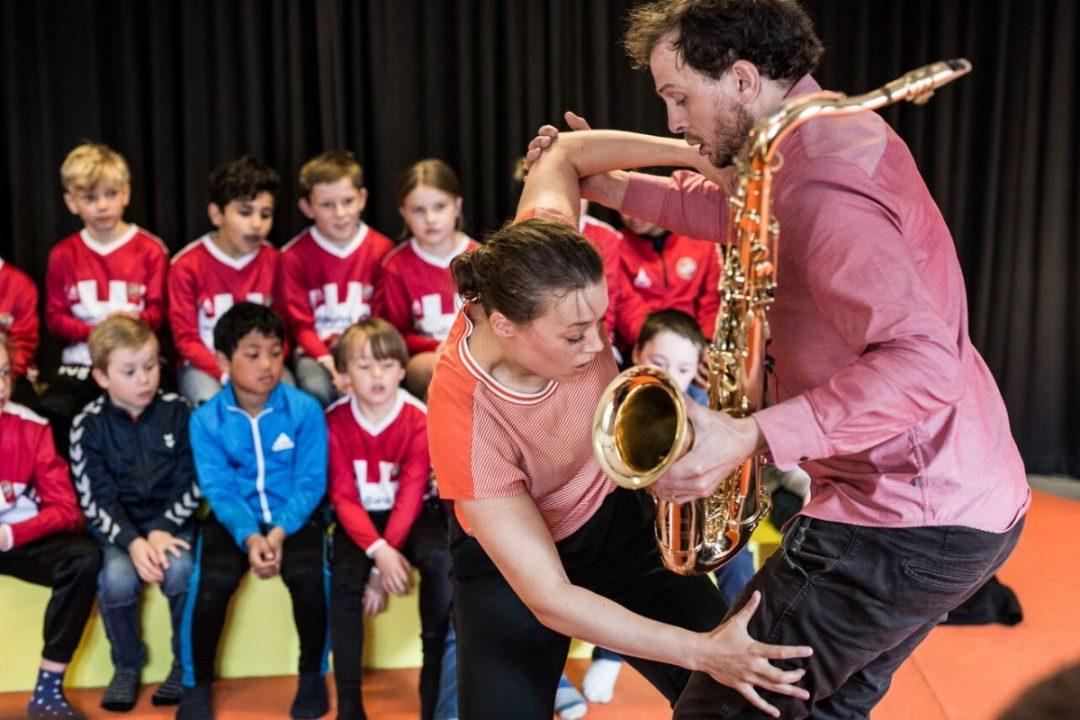 Kvinnelig danser og mannlig saksofonist har forestilling for skolebarn.