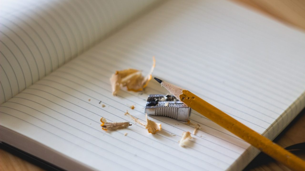 Bildet av en tom notatblokk med en gul blyant, en blyantkvesser og rester av kvessing.