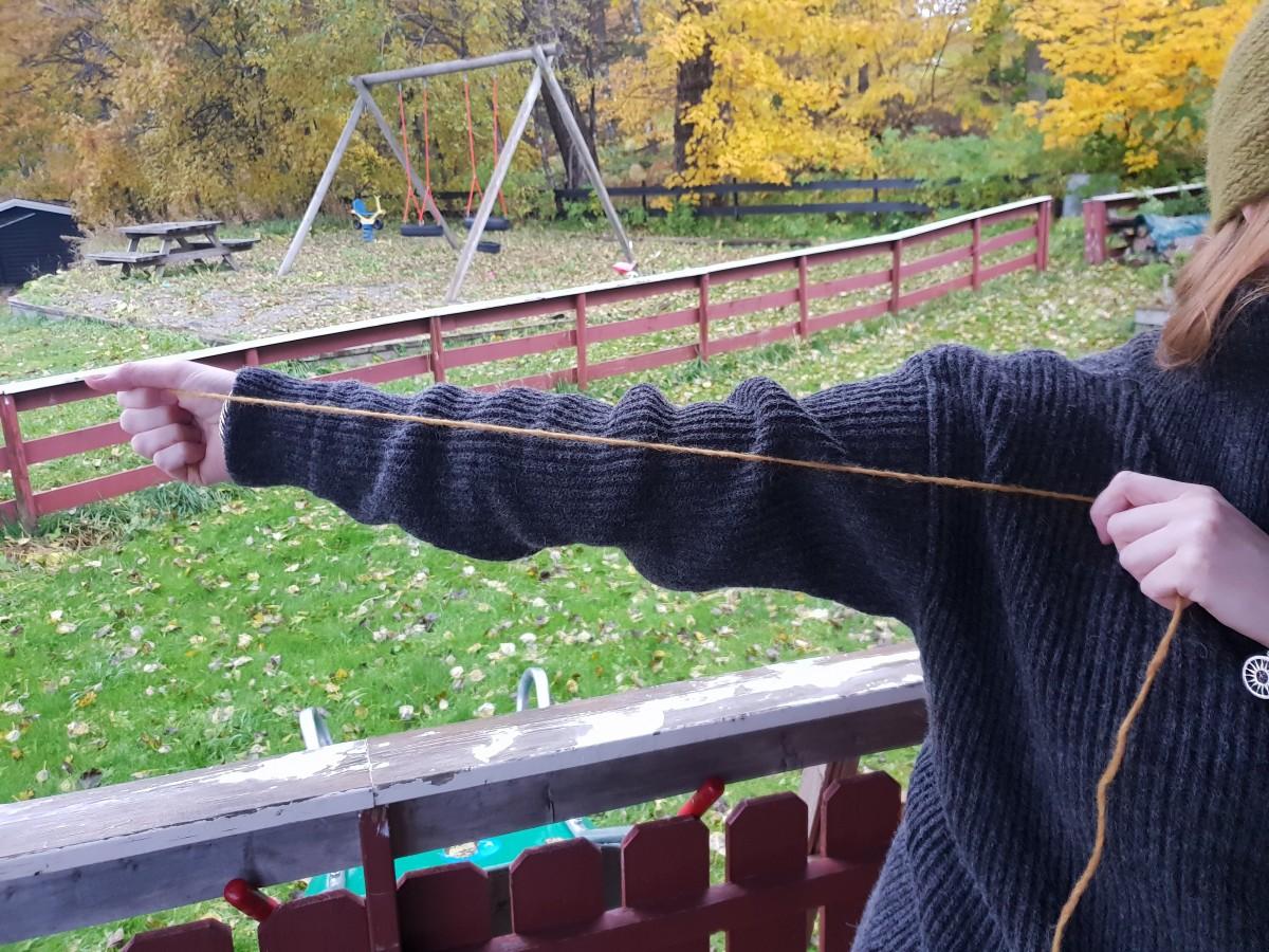 Viser hvordan man måler garnlengde med armen.
