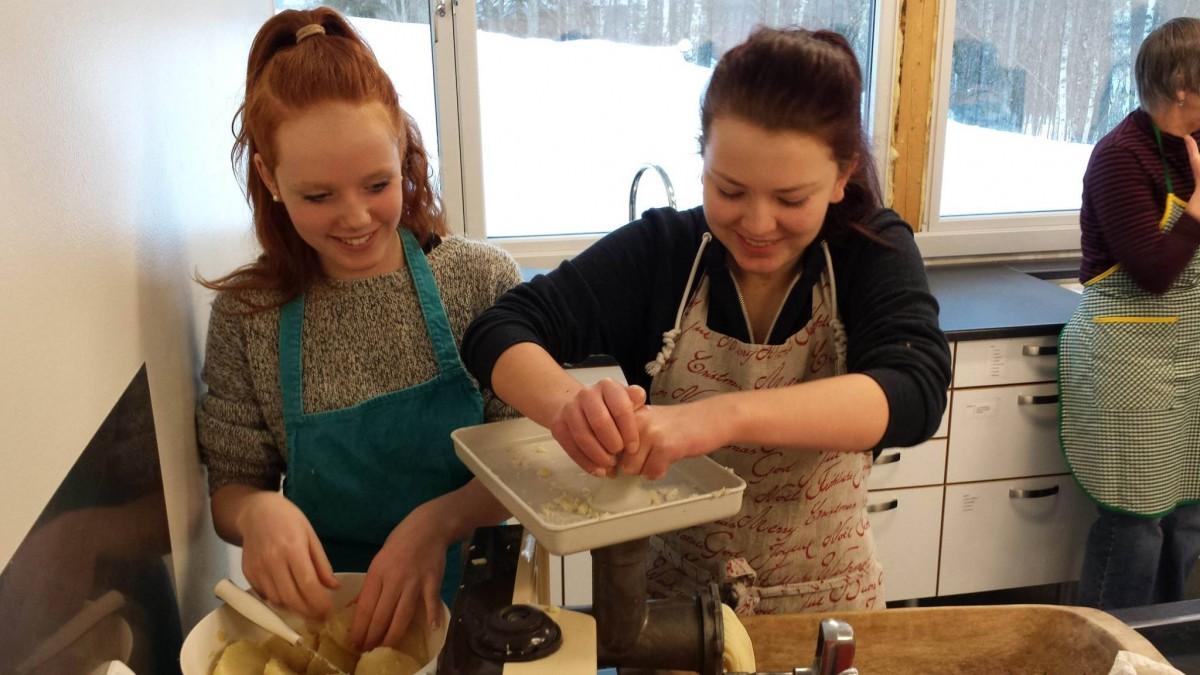 To ungsdomsjenter maler poteter med kjøkkenmaskin.