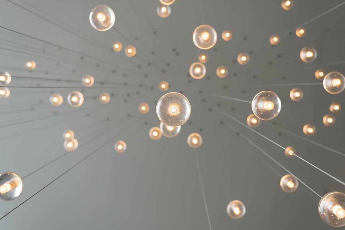 Bilde av mange lyspærer mot et grått tak.