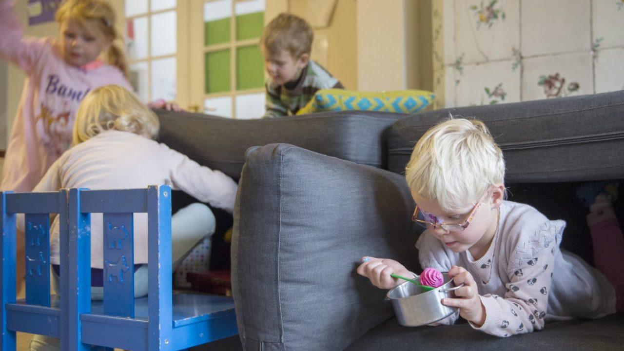 Barn bygger hytte med sofaputer.