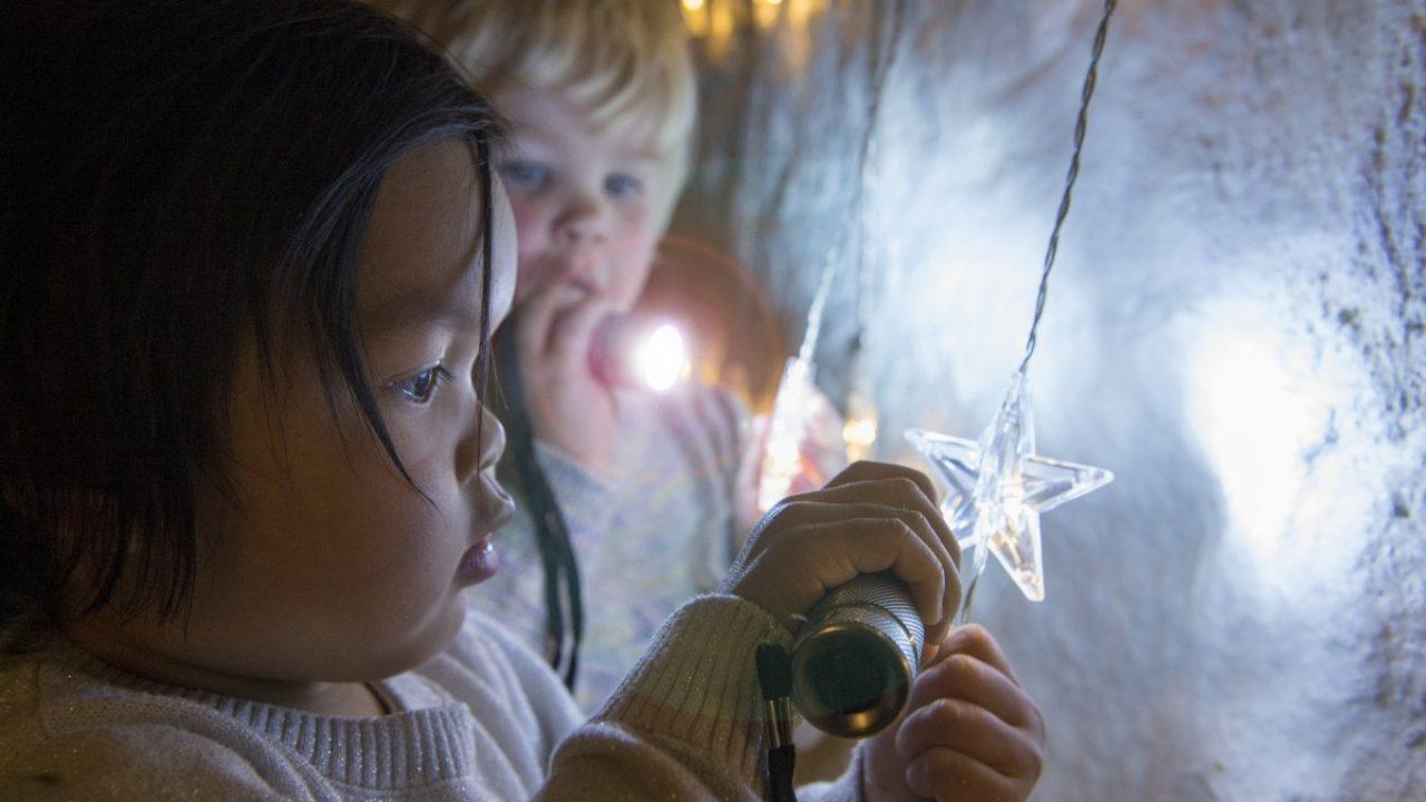 Barn lyser med lommelykt på en strejernfigur.