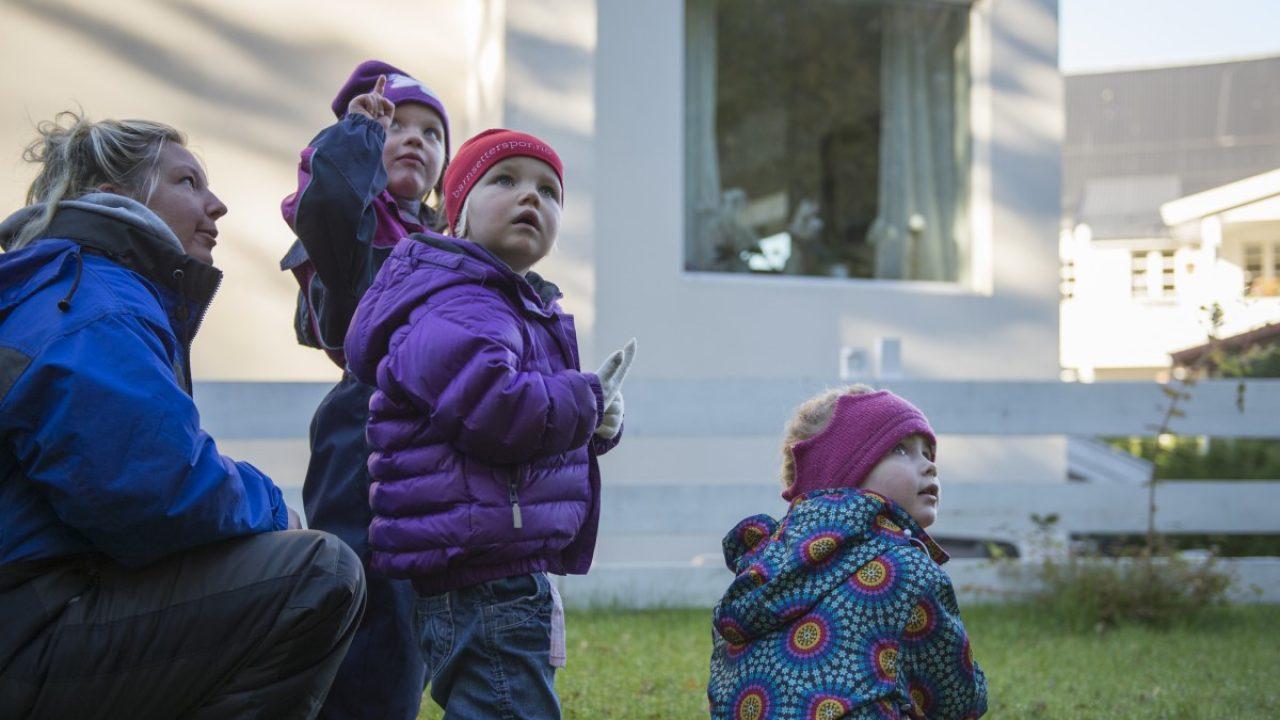 Tre barn og en voksen studerer en bygning i nærmiljøet.