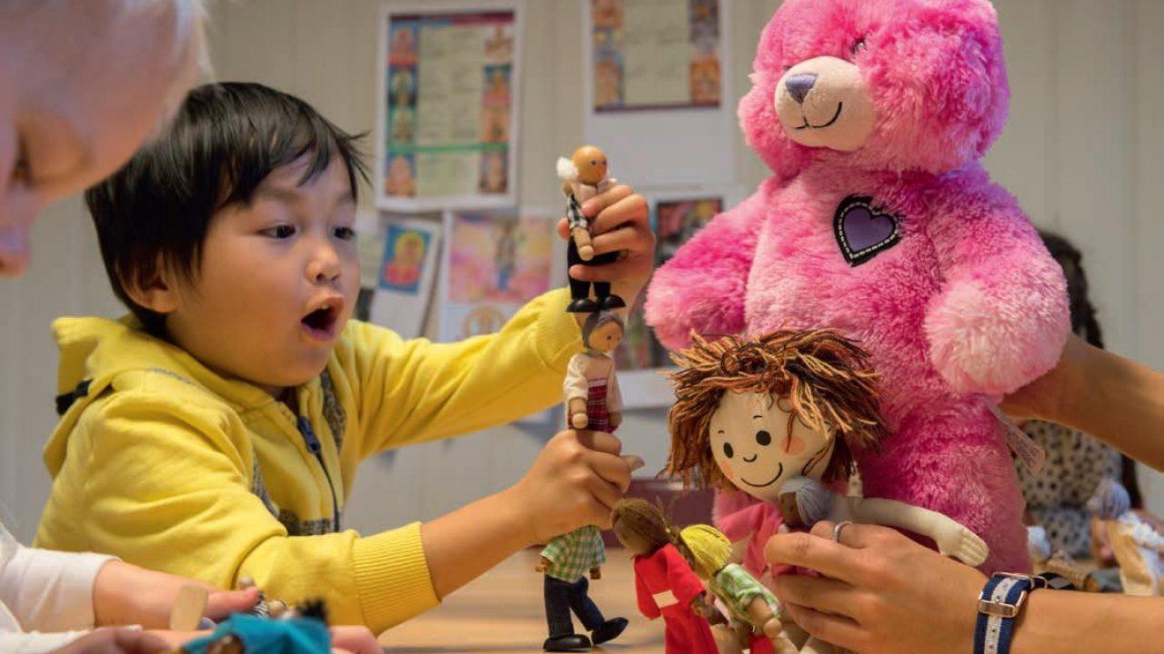 Barn som leker med dukker.