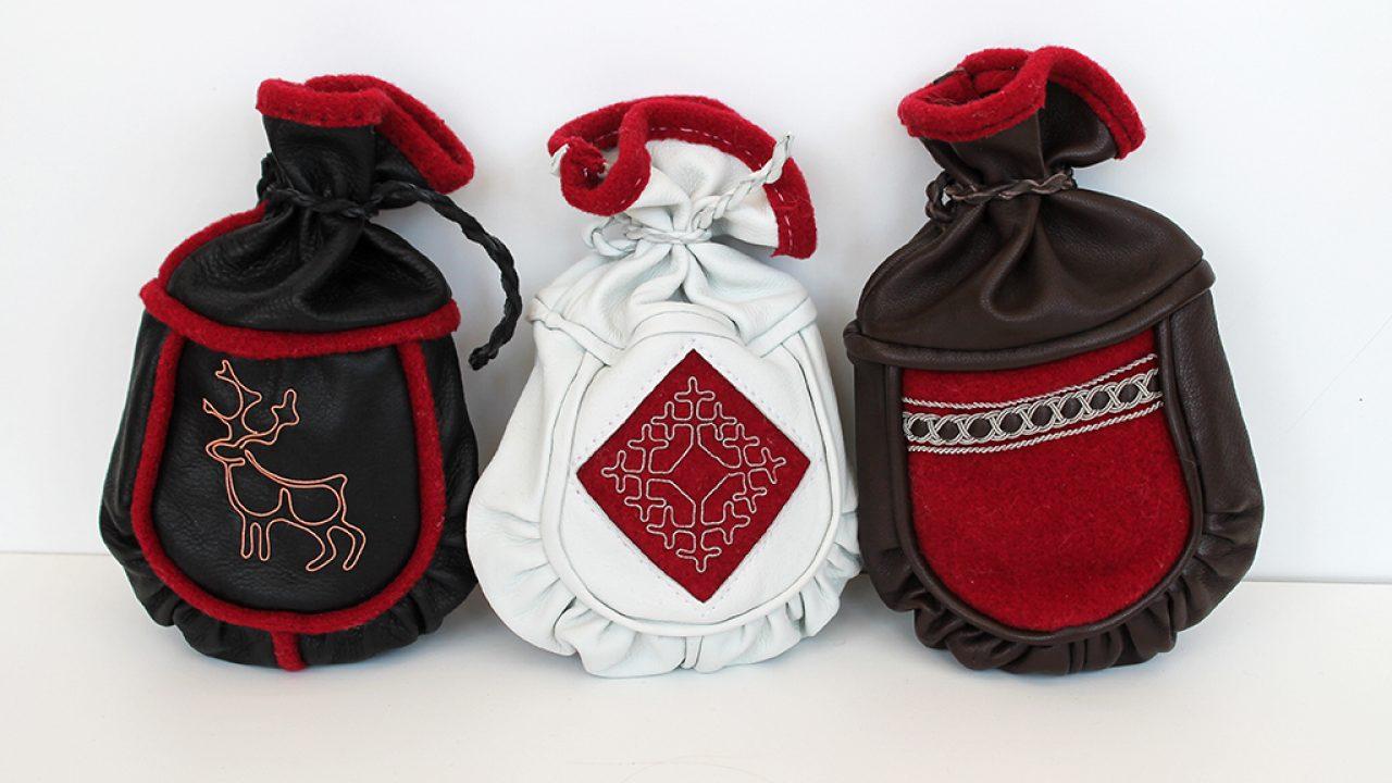 Tre kaffeposer laget i garvet reinskinn og lammeskinn. Dekor utført i tinntrådebroderi.