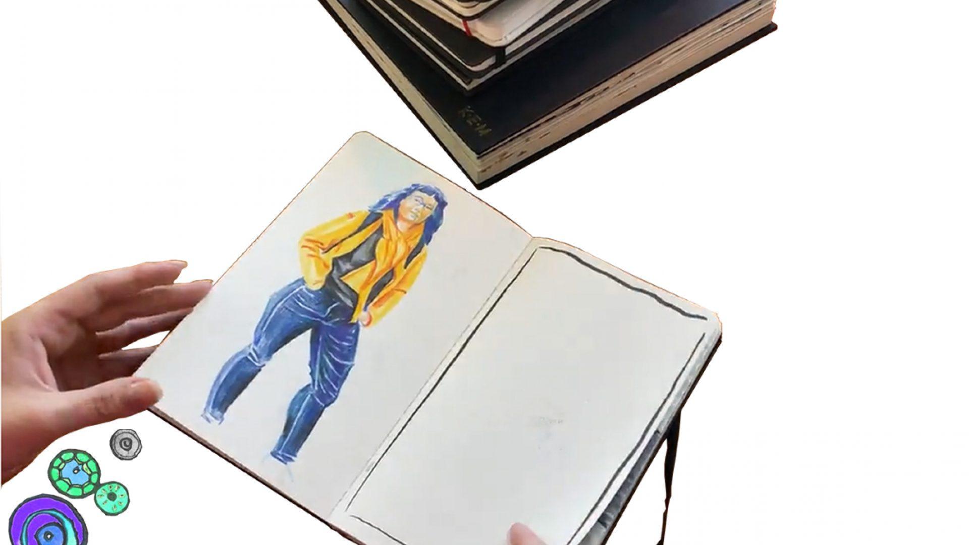 Hånd som holder en skissebok.