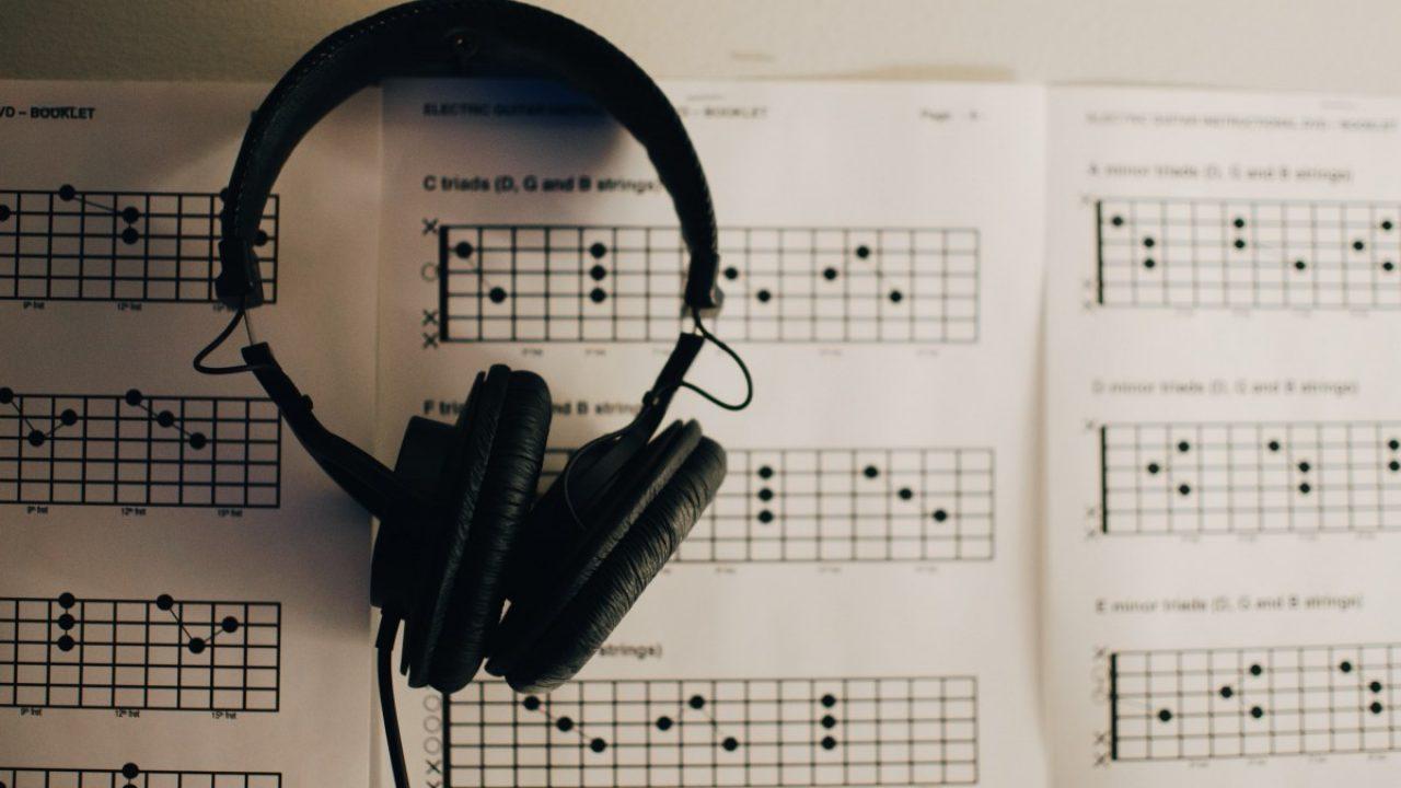 Svart headsett framfor hvite ark med musikkteori. Foto