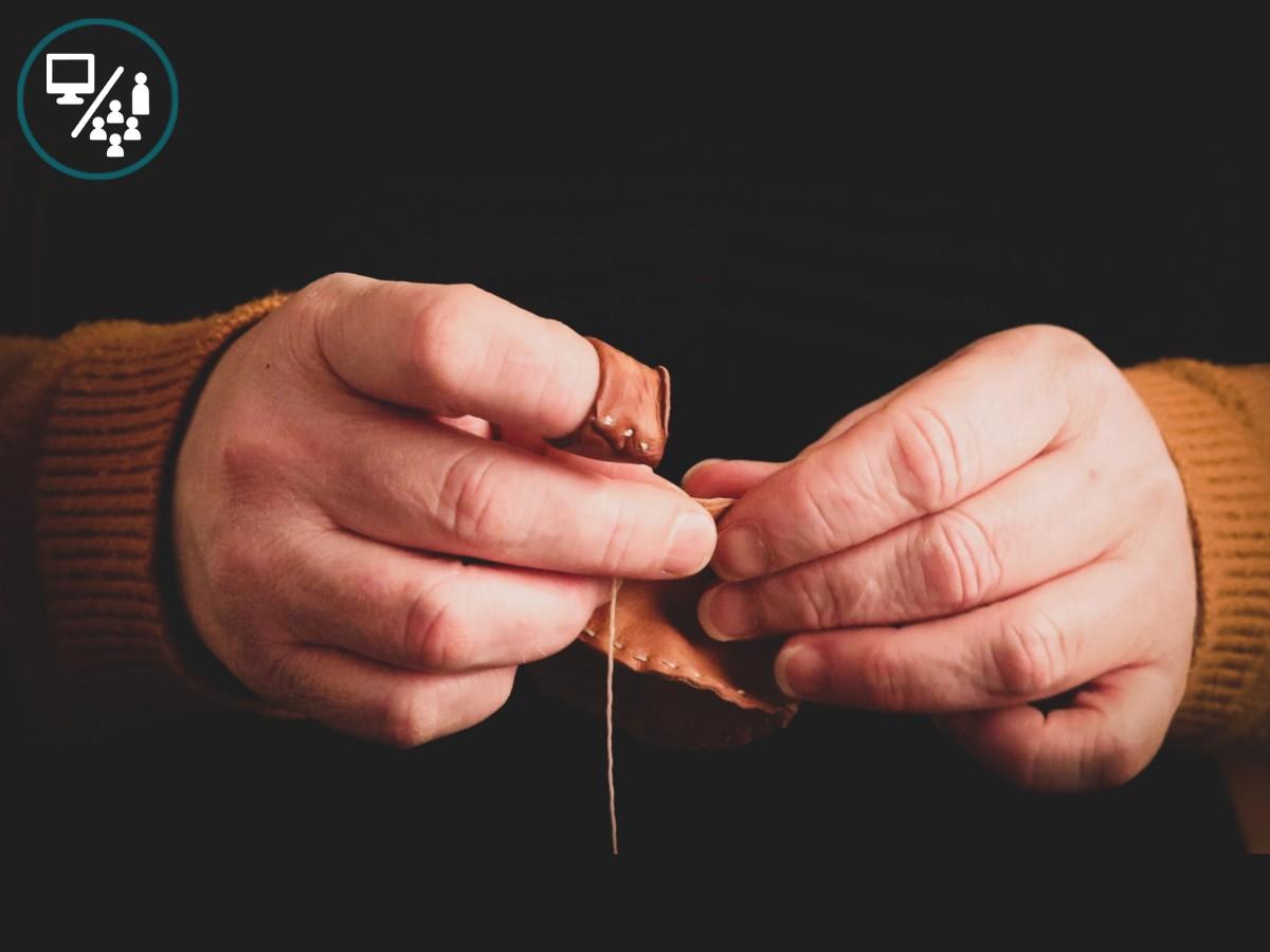 Illustrasjonsbilde av hender som syr, svart bakgrunn.