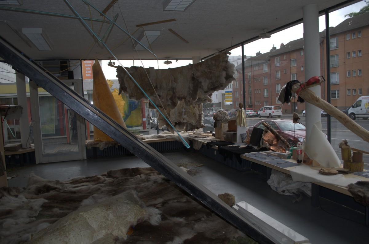 Skinnfeller av reinskinn og andre materialer satt opp i en glasspaviljong.