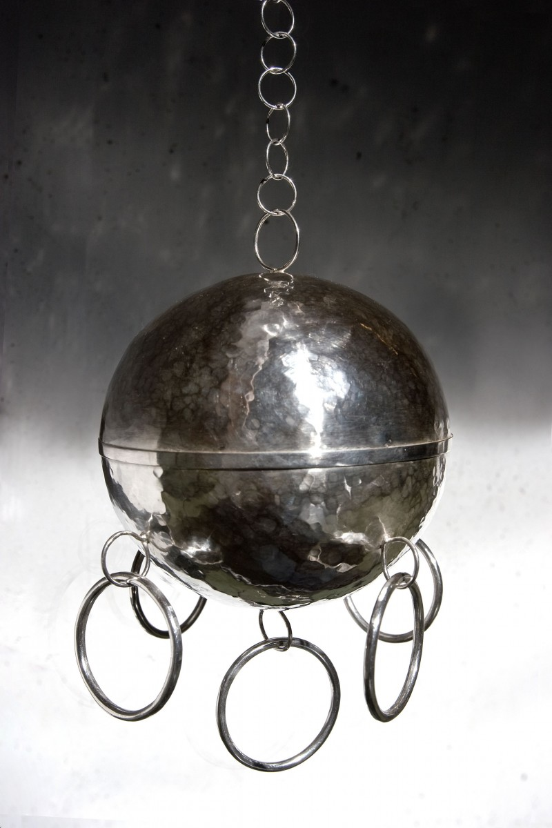 Stor sølvkule, hengende i et kjede. På kulens nederste hemisfære er det festet fem sølvringer. Foto.