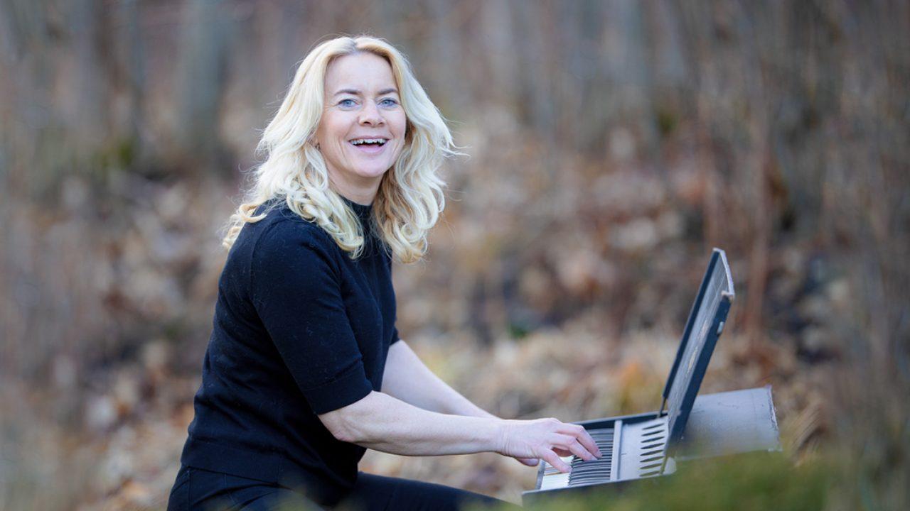 Bilde av kvinne som smiler og spiller piano i skogen