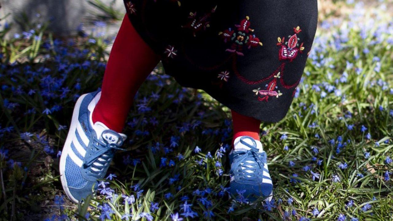 Føtter i joggesko og nederste del av en bunadstakk. Foto.