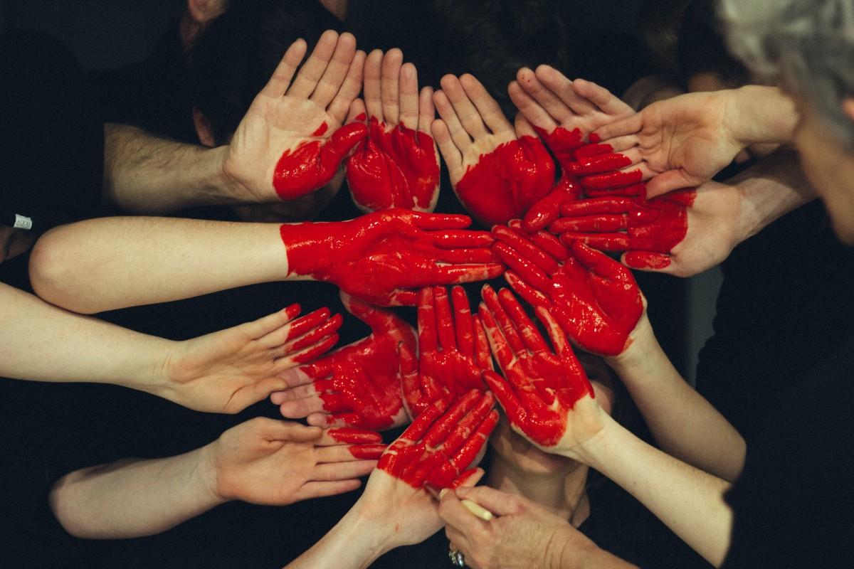 Hender som holdes inn mot midten med et malt rødt hjerte.
