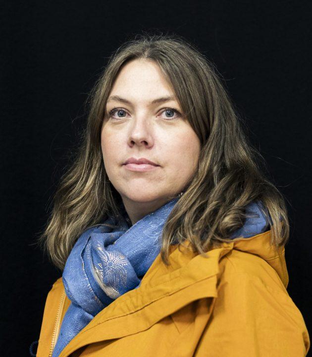 Kvinne med gul jakke og blått skjerf.