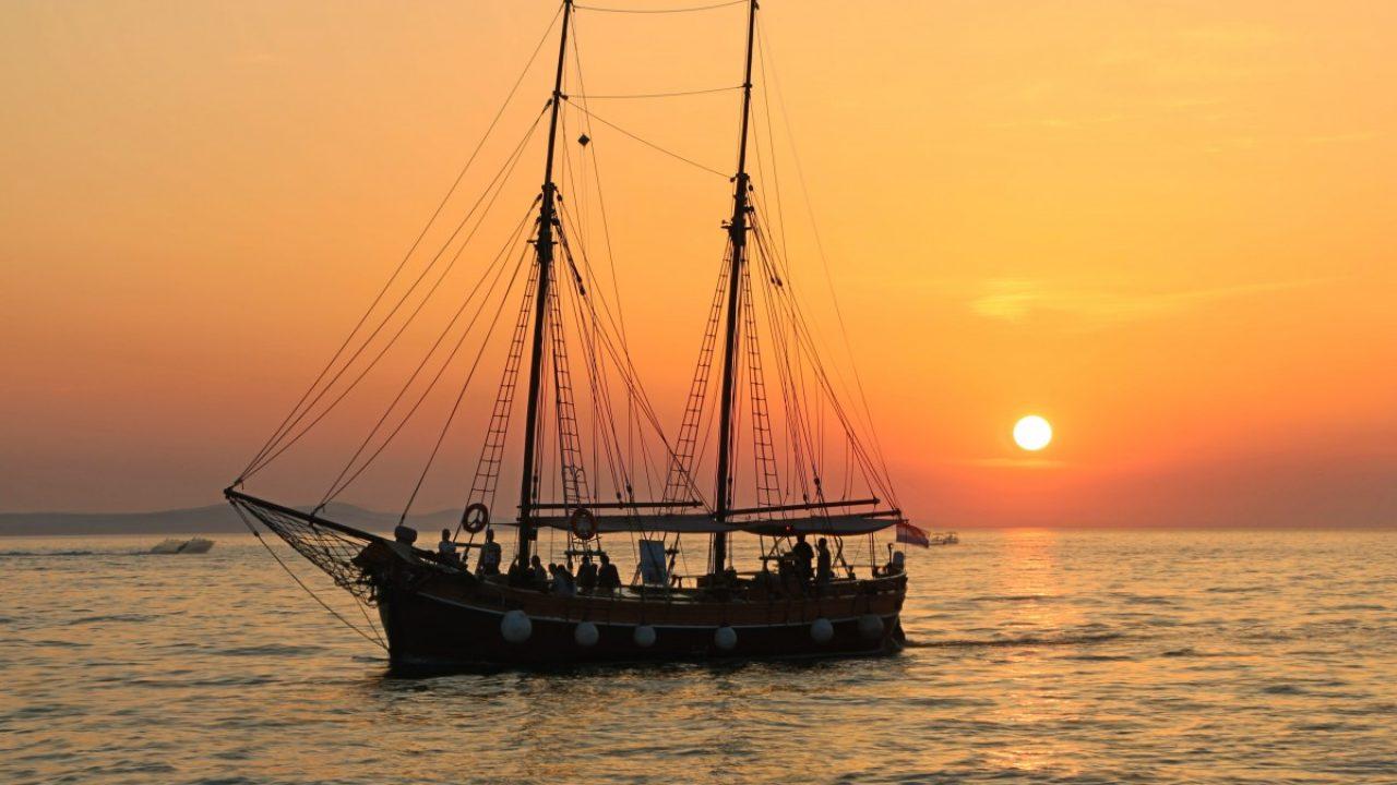 Skute som seiler på havet i solnedgagn